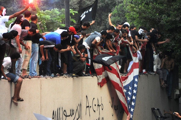 Egyptian protesters tear down the US flag at the US embassy in Cairo (Newscom)