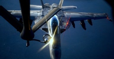 A U.S. fighter jet refuels from an Air Force KC-135 Stratotanker Aug. 21., 2014 over the Central Command area of responsibility. (Photo: Staff Sgt. Shawn  Nickel / Flickr / Edited Daily Signal / CC BY-NC 2.0)