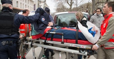 An injured person gets carried away from the site by a stretcher outside the Charlie Hebdo office. (Photo: Lionel Urman/Newscom)
