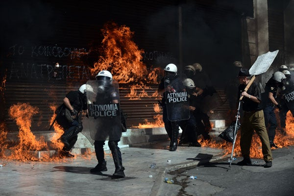 A fire bomb explodes behind a riot police squad on September 26 in Athens, Greece, during clashes with demonstrators. (Photo: AFP)
