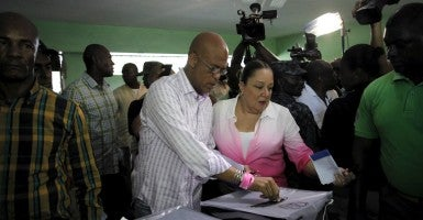 Haiti's President Michel Martelly (C) casts his vote next to his wife Sophia (R) at a polling station in Port-au-Prince, Haiti, August 9, 2015 (Photo: Stringer /Reuters /Newscom)