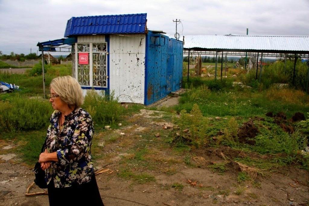 Alexandra, 63, waits for a bus in Semyonovka, the scene of intense fighting between Ukrainian and combined Russian-separatist forces in summer 2014. (Photo: Nolan Peterson/The Daily Signal)