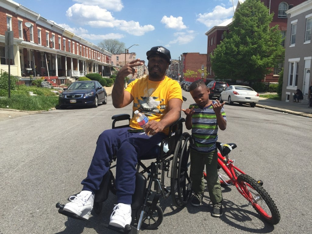 """Shakeebe McKoy, an East Baltimore resident visiting his family in West Baltimore, imparts a """"realistic"""" brand of parenting on his young son, Craig. (Photo: Josh Siegel/The Daily Signal)"""