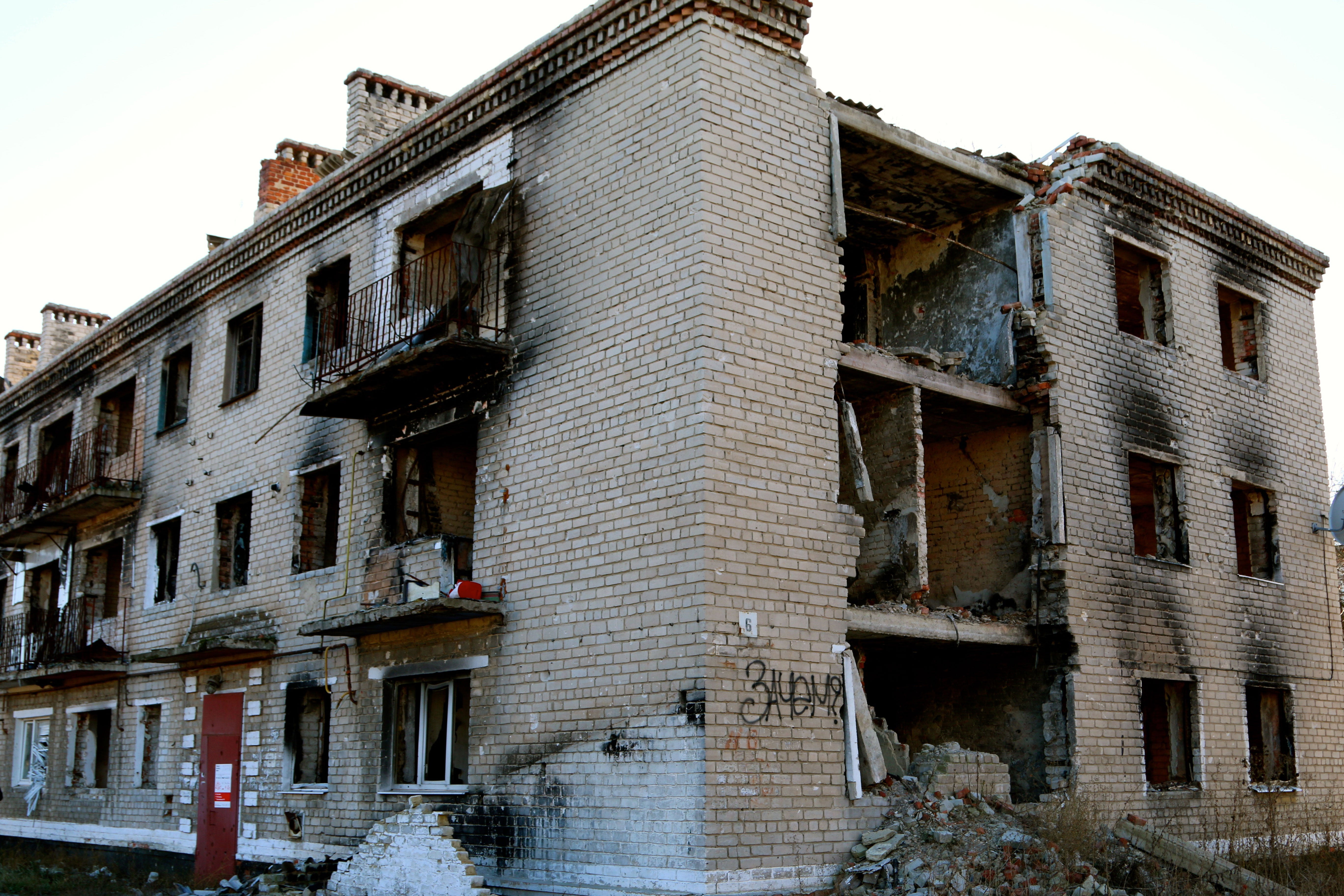 "An artillery-blasted apartment building in Marinka is marked by a spray-painted word in Russian, which translates to ""For what?"""