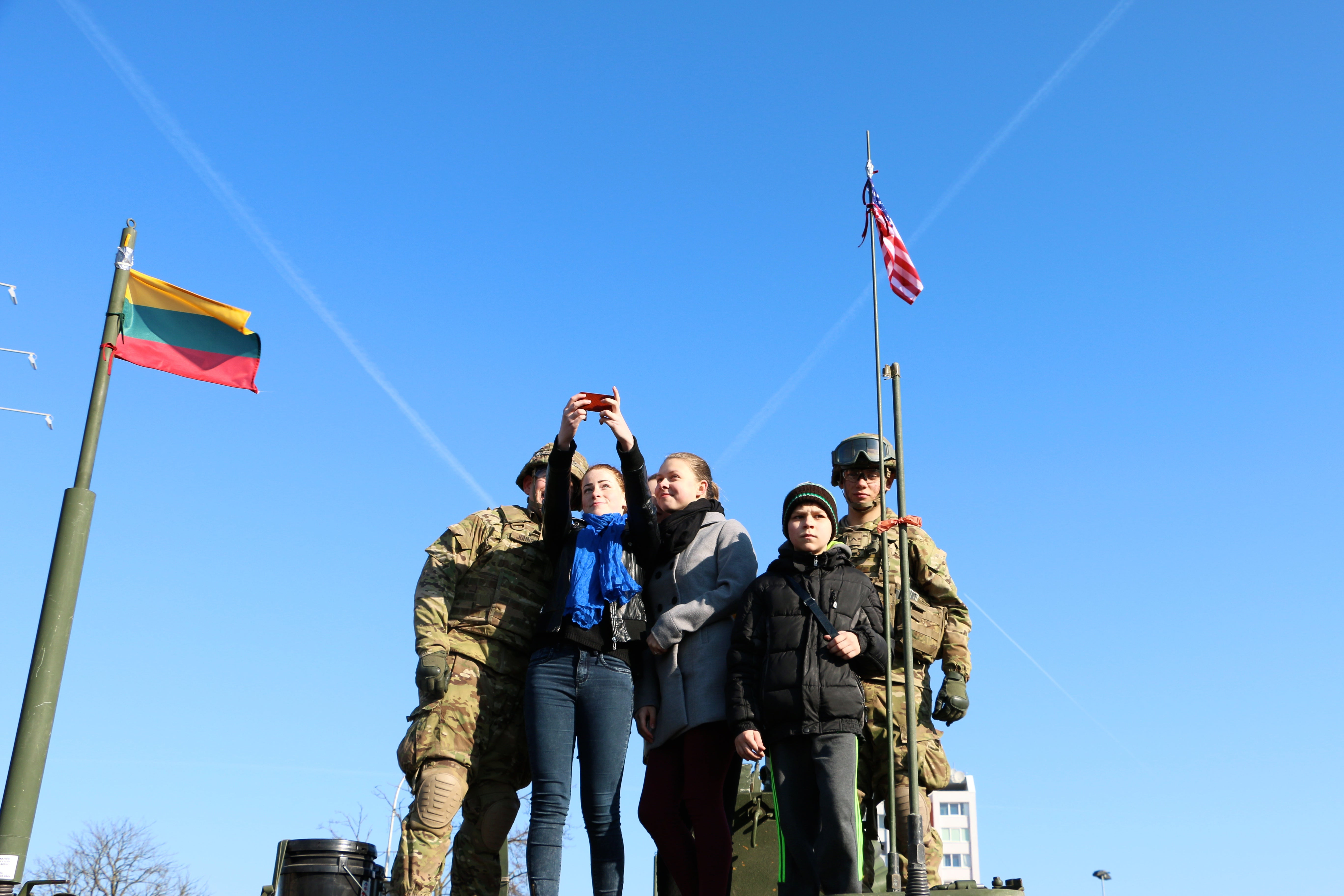 Lithuanians pose with U.S. Army soldiers at a U.S. Army Stryker static display in Marijampole, Lithuania on March 24.(Photo: Nolan Peterson/The Daily Signal)