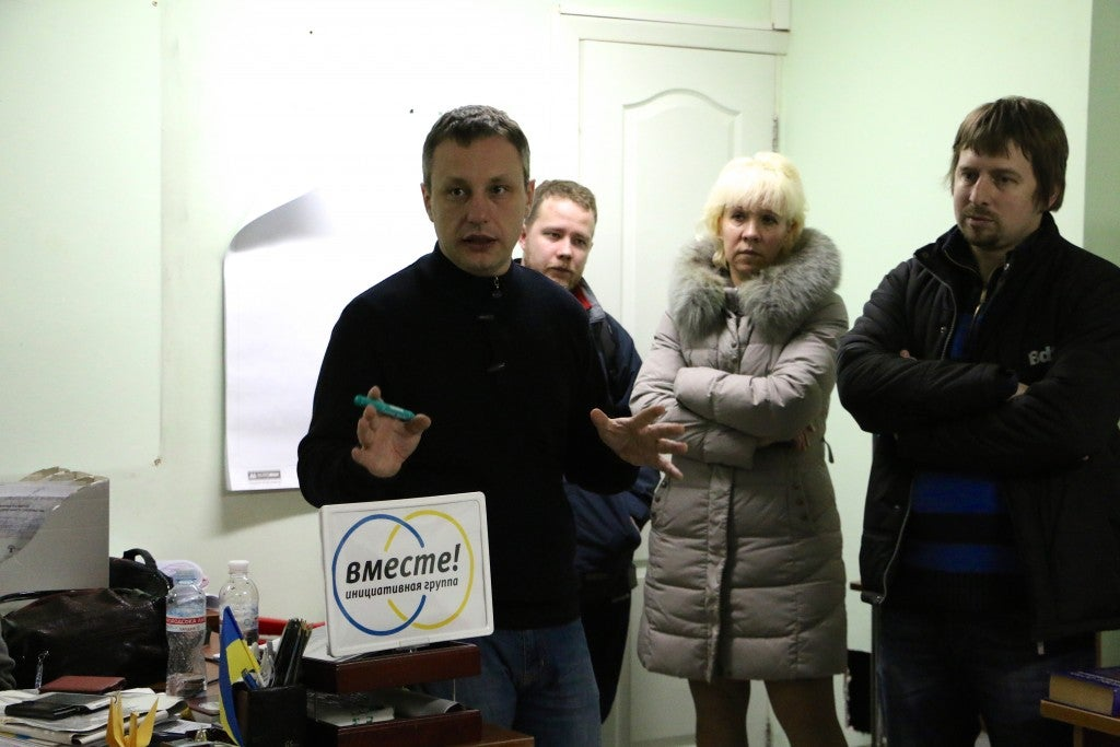 Peter Andrushchenko (left) and Maksim Borodin (far right) leading a discussion on democracy in a Mariupol basement. (Photo: Nolan Peterson/The Daily Signal)