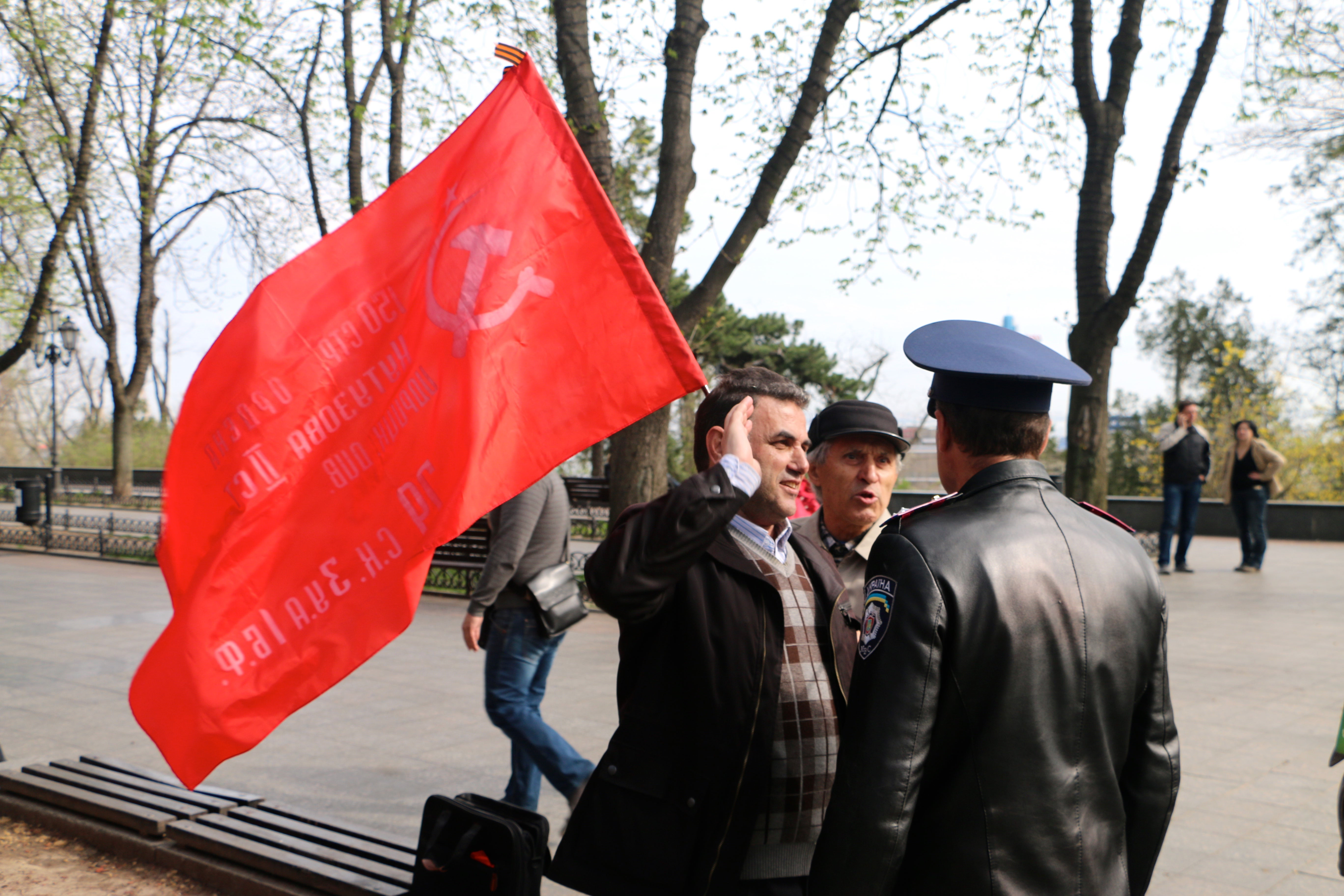 A police officer tells Communist Party members to put away a Soviet flag in Odessa, Ukraine. (Photo: Nolan Peterson/The Daily Signal)