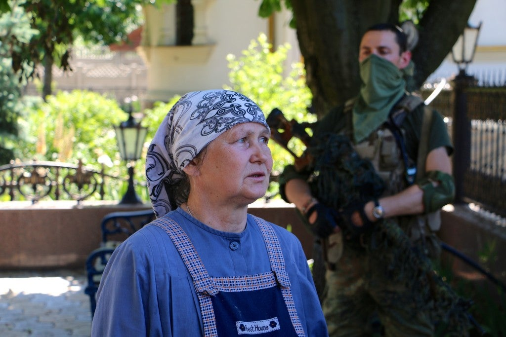 An Orthodox nun hands out chocolate and water to Ukrainian soldiers. (Photo: Nolan Peterson/The Daily Signal)