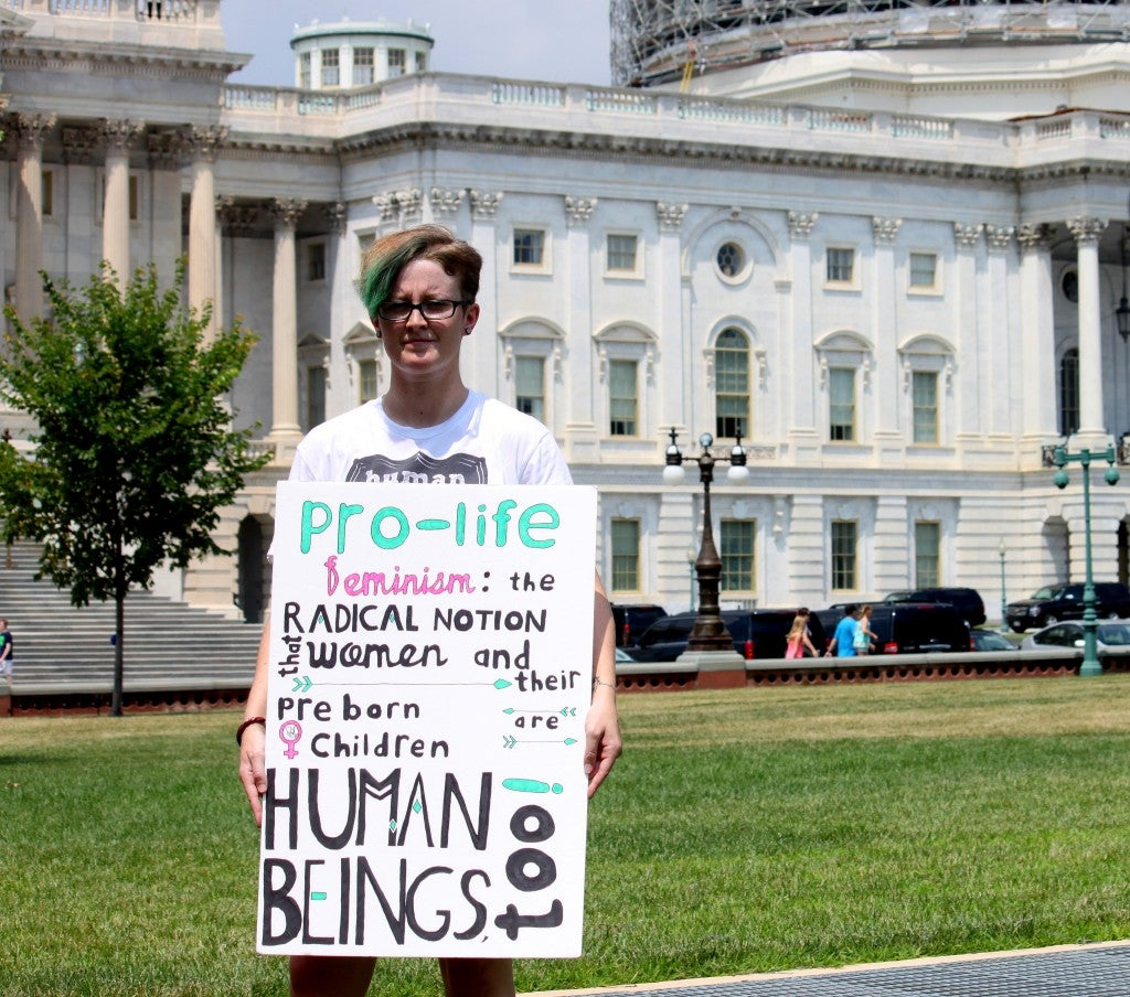 """Twig, 26, has been a part of the pro-life movement since she was 14 years old. """"I see something wrong and I just decide I'll make a sign about it, although this one was made by someone who has better handwriting than I do,"""" Twig said. (Photo: Samantha Reinis/The Daily Signal)"""