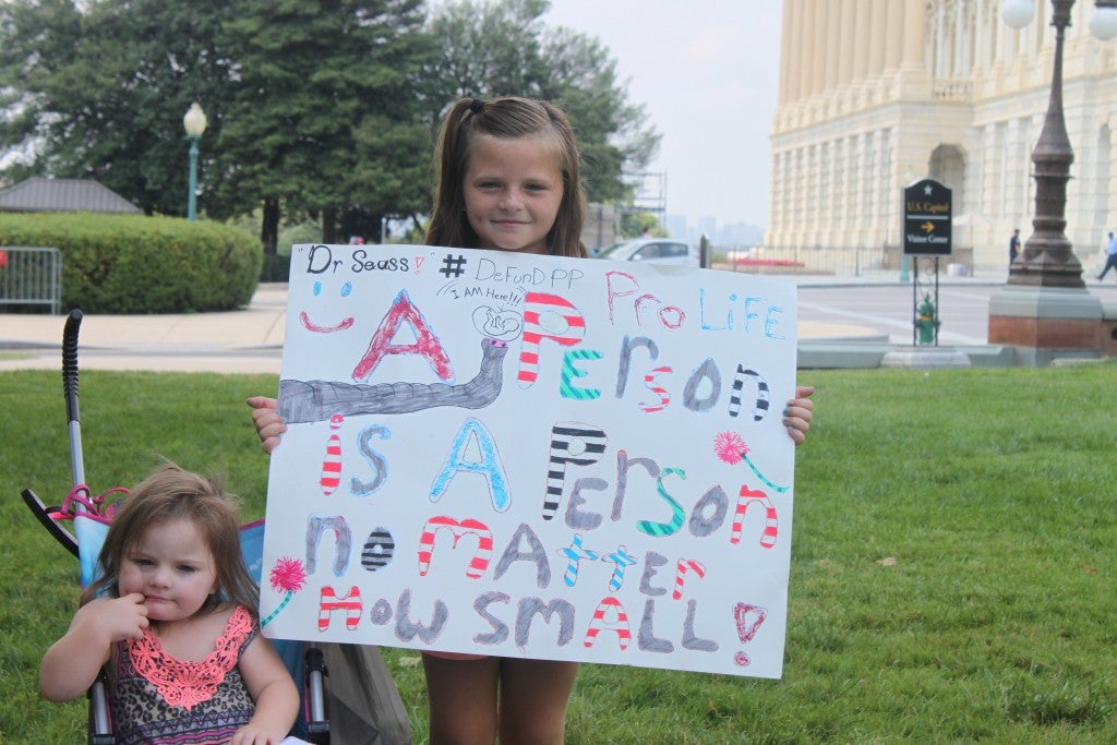 """Mary-Kate and Audrey Groman stand with their handmade Dr. Suess' Horton Hears a Who! themed sign. """"She liked it because it was about small people-looking out for the tiny ones,"""" her mother, Mary said. (Photo: Samantha Reinis/The Daily Signal)"""