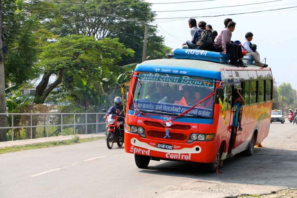 Many in Nepal ride on the roofs of buses when seats inside fill up. (Photo: Nolan Peterson/The Daily Signal)