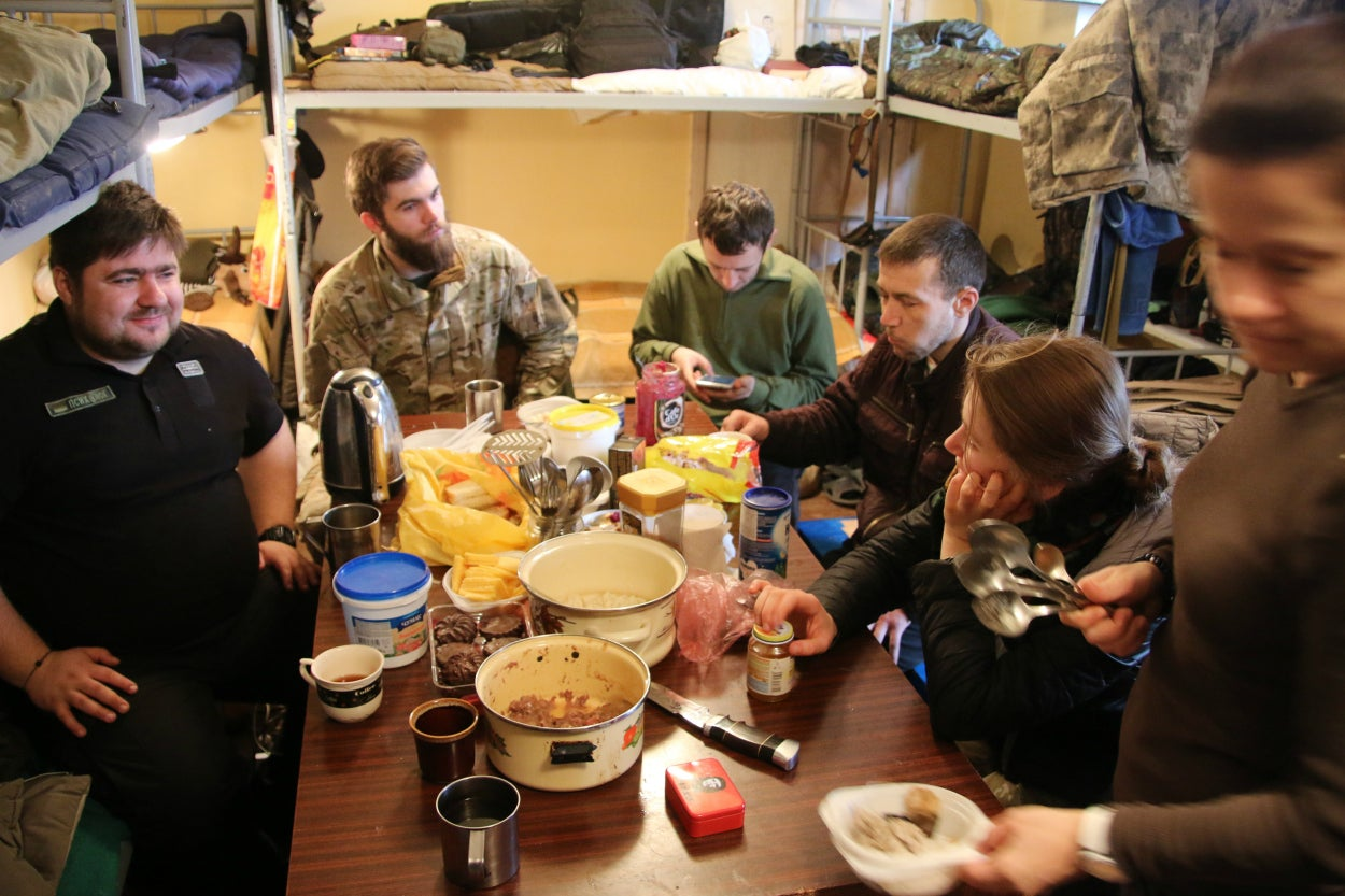 A team of Ukrainian volunteer psychologists and veterans share breakfast at a Ukrainian National Guard base in eastern Ukraine.