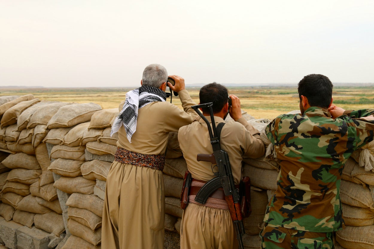Peshmerga soldiers observe ISIS positions at a front line position south of Mosul.