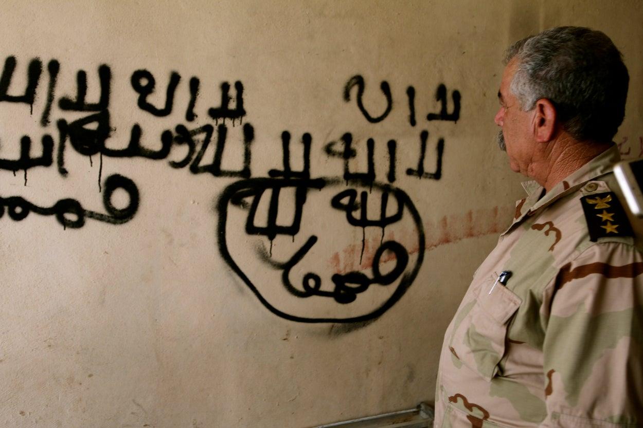 Peshmerga Col. Shuqur Qasim Yusif in front of ISIS graffiti.