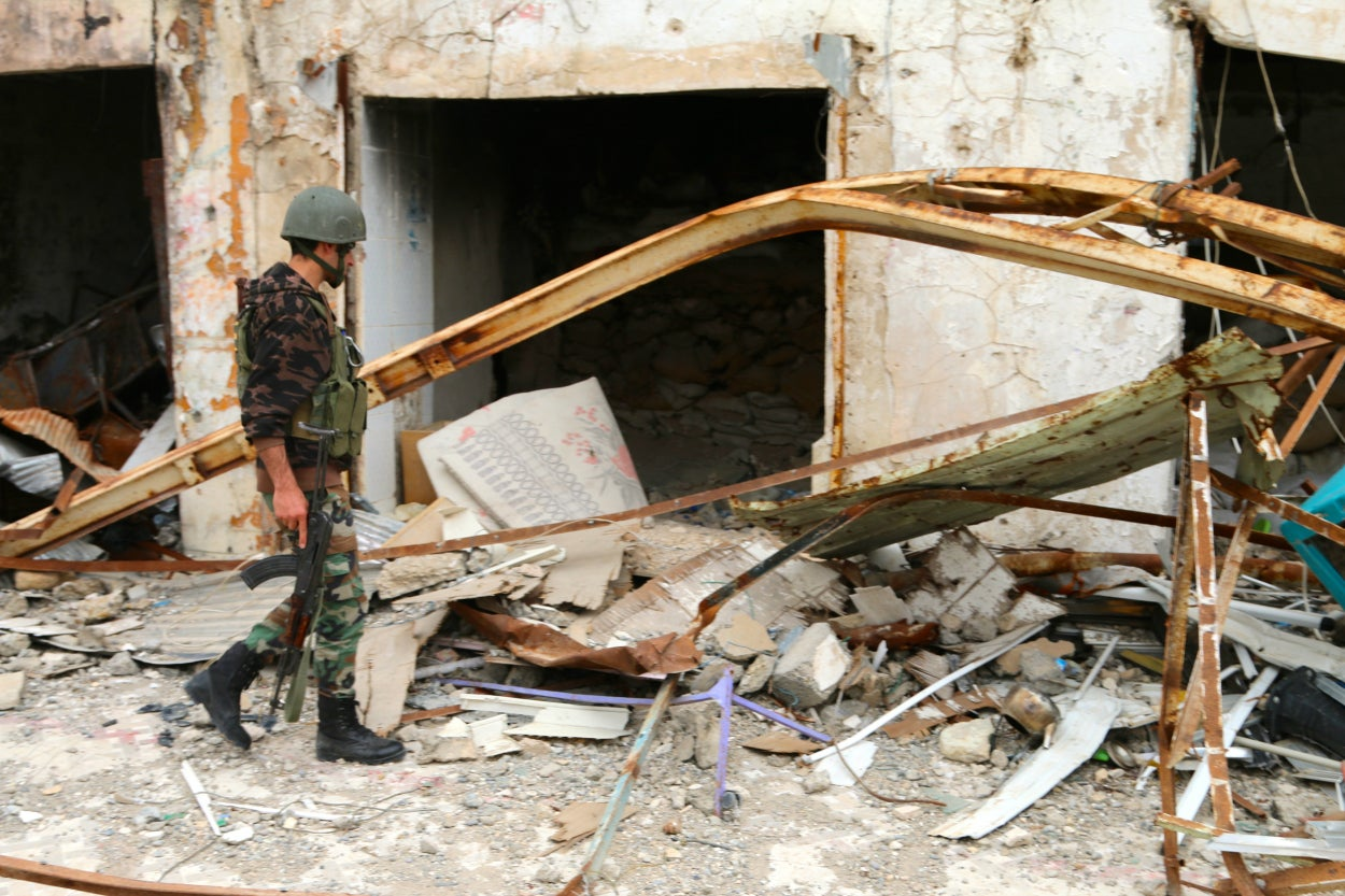 ISIS attacks Sinjar almost daily with artillery and rockets; Kurdish peshmerga soldiers are on guard.