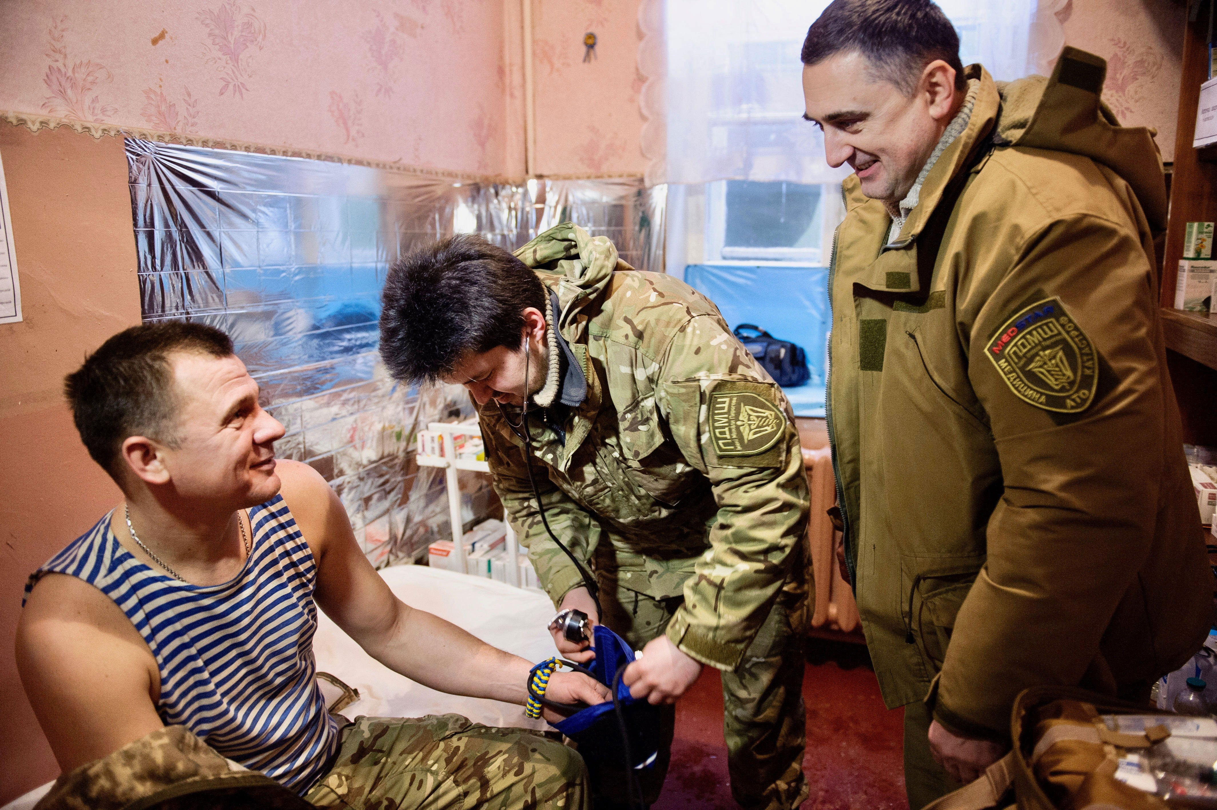 Oleg Zinevych, right, and Pavlo Orynchak, center, treat a Ukrainian soldier in Volnovakha. (Photo: Olga Ivashchenko)