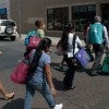 Young women and their children leave a Catholic Charities center July 23 on t