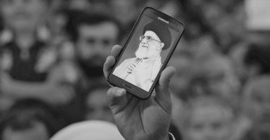 An Iranian man holds his mobile phone showing a picture of Iranian supreme leader Ayatollah Ali Khamenei as he along with others attends the ceremonies on the occasion of the 26th death anniversary of Ayatollah Ruhollah Khomeini (Photo: ABEDIN TAHERKENAREH/EPA/Newscom)