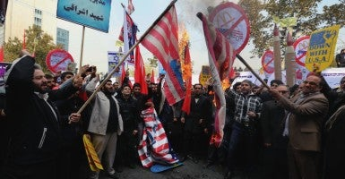 Iranian protesters burn mock American flags during a demonstration marking the 36th anniversary of US Embassy seizure, in front of the former US embassy in Tehran, Iran,  Nov. 4 2015. Thousands of protesters chanting 'Death to America' gathered at the former US embassy in Tehran to mark the 36th anniversary of the start of the Iran hostage crisis.  (Photo: STR/EPA/Newscom)