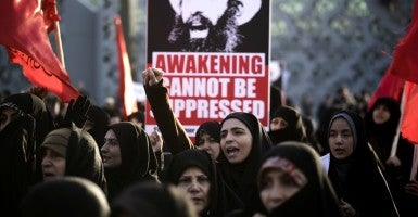 An Iranian veiled woman shouts anti-Saudi Arabia and anti-U.S. slogans as a placard with a portrait of the executed Shia cleric Sheikh Nimr al-Nimr is seen in background during a rally at a square in southern Tehran on Jan. 4, 2016. Tehran, Iran. (Photo: Morteza Nikoubazl/SIPA/Newscom)
