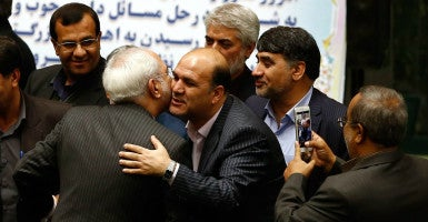 Parliament members congratulate Iranian Foreign Minister Mohammad Javad Zarif after some international sanctions against Iran were lifted as part of a nuclear deal. (Photo: Abedin Taherkenarhh/EPA/Newscom)