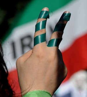 Iranian Protesters Hold Up Green Flags and Ribbons
