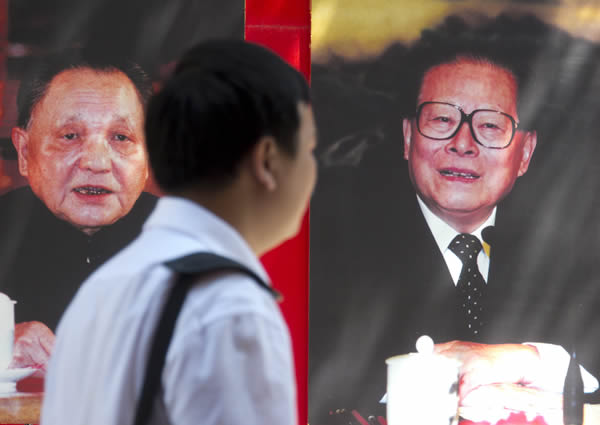Man walks by poster of Jiang Zemin