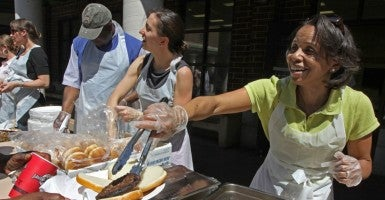 Wilhelmina Marie Wright, right, serves up hamburgers in May 2010 to hundreds of people at the Dorothy Day Center in St. Paul, Minn. (Photo by Bruce Bisping/Star Tribune/Newscom)