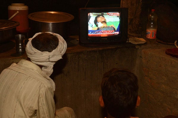 Pakistani villagers in his village watch the news on television of Ajmal Kasab, who was executed in an Indian prison. (Photo: AFP/Newscom)