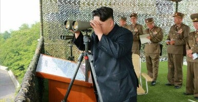 North Korean leader Kim Jong-un using binoculars to watch an anti-aircraft shooting contest at an undisclosed location, North Korea. (Photo: RODONG SINMUN/EPA/Newscom)