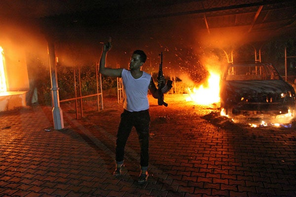 An armed man waves his rifle as buildings and cars are engulfed in flames after being set on fire inside the US consulate compound in Benghazi late on Sept. 11, 2012. (Photo: Getty Images/Newscom)