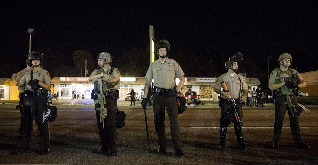 Police officers in riot gear stand guard during a protest in Ferguson. (Photo: Xinhua/Ting Shen)