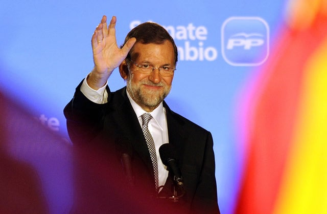 Leader of the Spanish Popular Party (PP) Mariano Rajoy (C) waves to supporters from the balcony of the PP headquarters in Madrid on November 20, 2011, after the first results of the general elections were announced.