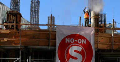 "A Los Angeles construction worker works on site by a ""No on S"" campaign sign expressing opposition to Measure S. (Photo: Mike Blake/Reuters/Newscom)"