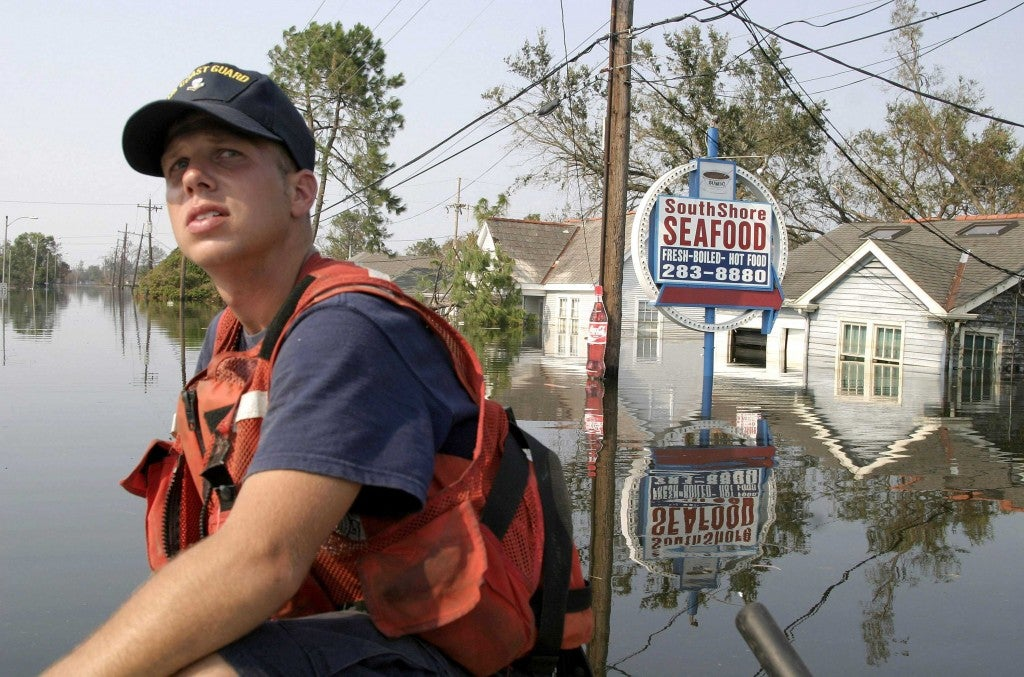US Coast Guardsman Neil Hebert surveys a stricken neighborhood during search and rescue operations in New Orleans. (Photo: Bartlett/SIPA/Newscom)