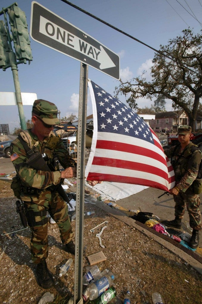 Two members of the National Guard put up the American flag amidst the rubble of the storm. (Photo: Haley/SIPA/Newscom)