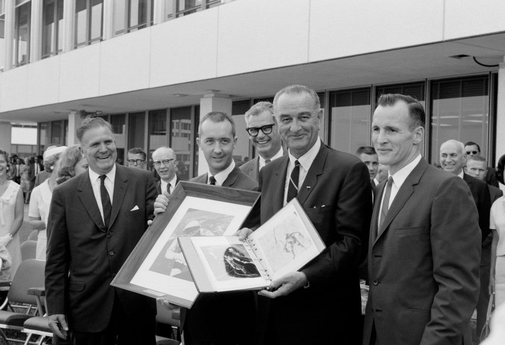 "President Johnson holds a Gemini-4 souvenir photo album which he was presented by Gemini-4 astronauts James A. McDivitt and Edward H. White II. McDivitt holds a framed picture of White's ""spacewalk"" which was also given the President. (Photo: NASA)"