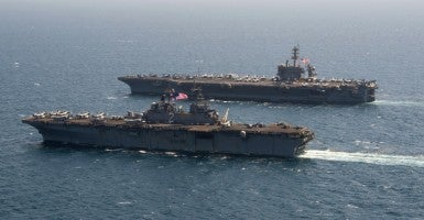 The Wasp-class amphibious assault ship USS Essex alongside the aircraft carrier USS Theodore Roosevelt in the Arabian Gulf. (U.S. Navy photo by Mass Communication Specialist 2nd Class Chris Brown/Released)