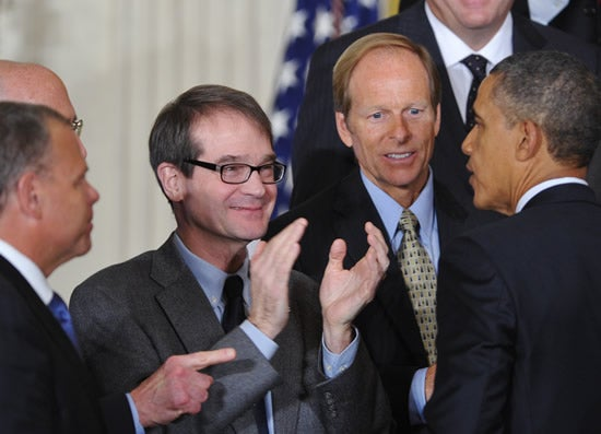 UAW President Bob King (C) applauds President Barack Obama on January 11, 2012, in the White House.