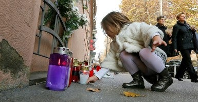 A young girl places a candle outside the French Embassy in Zagreb, Croatia, November 14. (Photo: Antonio Bat/Newscom)
