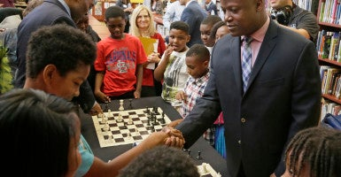 Chess grandmaster Maurice Ashley (right) teaches children at Walnut Grove Elementary in Ferguson, Mo., how to play chess. (Photo: Ascension)
