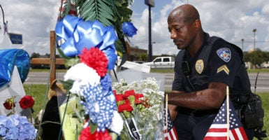 Cpl. Joseph Keller of the Baton Rouge Police Department pays his respects at a makeshift memorial where three police officers were shot and killed on July 19. (Photo: Jonathan Bachman/Reuters/Newscom)