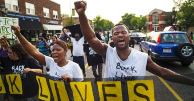 Rashad Turner (far right) led dozens of Black Lives Matter protesters in the neighborhood around the governor's mansion on Summit Ave. in St. Paul, Minnesota, on Sept. 1, 2015. (Photo: Richard Tsong-Taatarii/Zuma Press/Newscom)