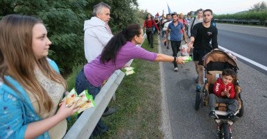 Sept. 4, 2015, Bicske, Hungary—People pass out provisions as hundreds of migrants walk along the motorway from Budapest north toward Austria. (Photo: Paul Hackett/ZUMA Press/Newscom)