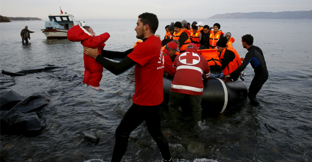 A Red Cross volunteer carries a Syrian refugee baby off a raft at a beach on the Greek island of Lesbos on Nov. 16. (Photo: Yannis Behrakis/Reuters/Newscom)