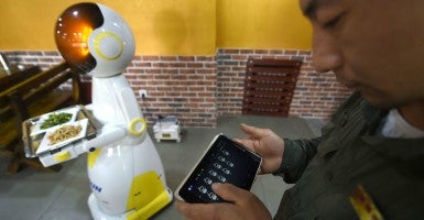 A waiter controls a robot to serve dishes at a restaurant in Shenyang, capital of northeast China's Liaoning Province, May 21, 2015 (Photo: CHINE NOUVELLE/SIPA/Newscom)