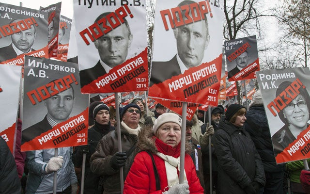 "Thousands of opposition protesters carry posters of President Vladimir Putin and members of the Russian parliament with the word ""Shame"" written in red. (Photo: Jeremy Nicholl/Polaris/Newscom)"