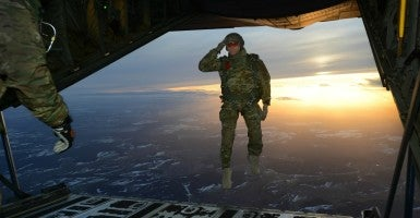 A U.S. Soldier assigned to 1st Battalion, 10th Special Forces Group (Airborne) salutes his fellow Soldiers while jumping out of a C-130 Hercules aircraft over a drop zone in Germany, Feb. 24, 2015. (Photo: The U.S. Army/Specialist Jason Johnston/ Flickr)