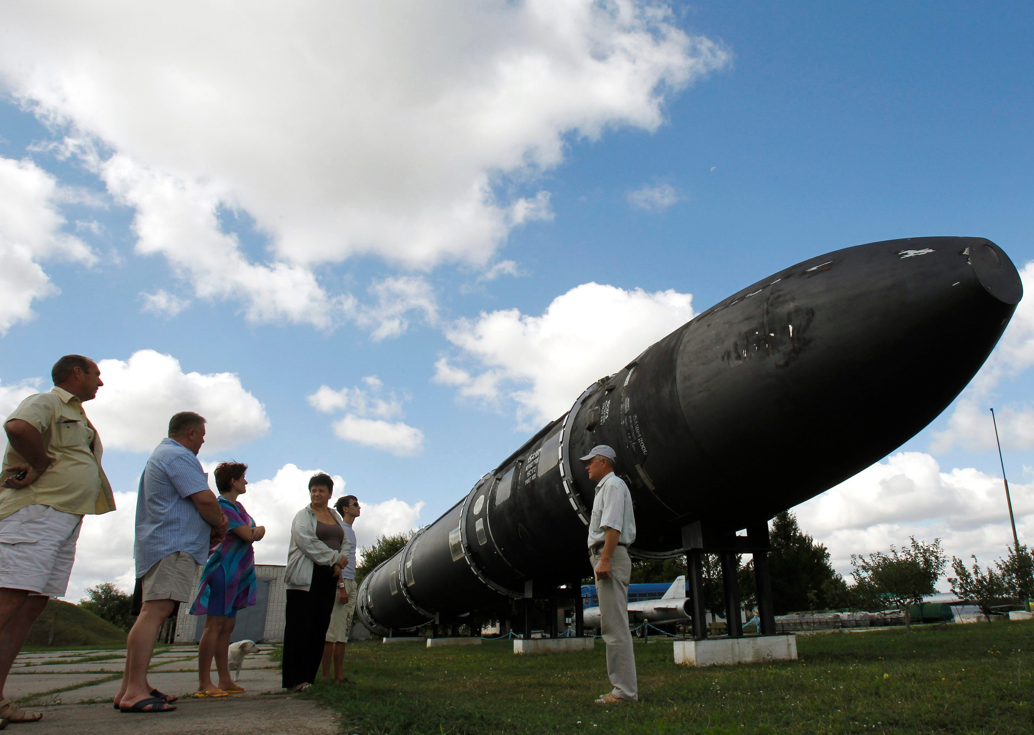 Visitors look at a SS-18 SATAN intercontinental ballistic missile at the Strategic Missile Forces museum near Pervomaysk