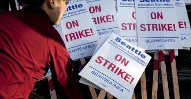 A teacher grabs a sign before walking the picket line as teachers strike outside Roosevelt High School in Seattle, Washington, September 9, 2015. (Photo: Reuters/Newscom/Matt Mills McKnight)